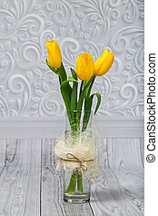 bouquet of yellow tulips in a simple glass vase