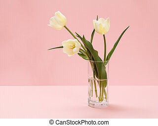 Bouquet of yellow tulips in vase on a pink background.