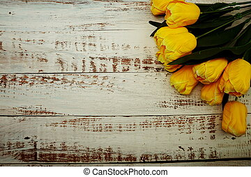 Bouquet of yellow tulips on white wooden background