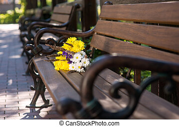 Bouquet on brown bench.