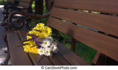 Bouquet on brown bench. White and yellow flowers. Lilac and...