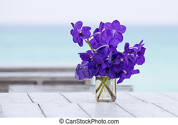 Bouquet orchids flower on a background of the sea in table