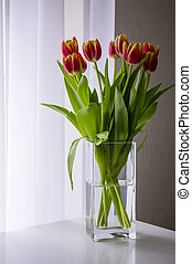 Bouquet tulip in a vase by the window.