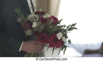 bouquet with flowers in the hands of the groom