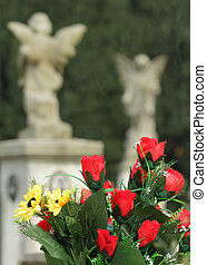 bouquet with red roses on old cemetery with angelic statues on t