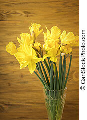 Bouquet Yellow daffodil in a glass vase on a wooden background. Copy space