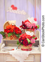Bouquets roses in a baskets on an old wooden dresser
