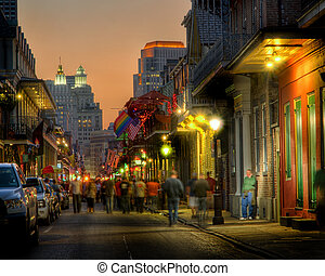 A view looking down the vibrant and colourful Bourbon Street, in the heart of the New Orleans French Quarter, just after sunset at the height of the October tourist season.
