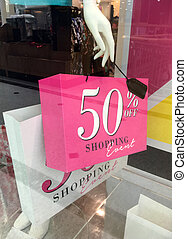 Boutique mannequin holding sale sign on shopping bag