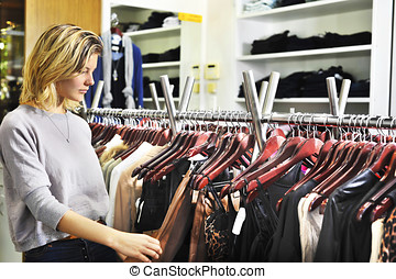 boutique shopper browsing - a young woman looks at a skirt...