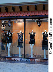Boutique window with dressed mannequins in shopping mall