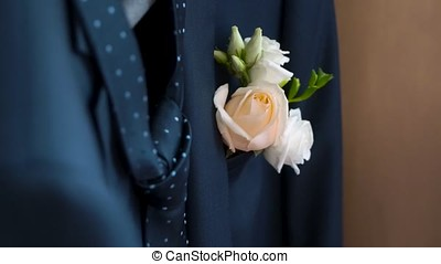 Boutonniere in the pocket of the jacket of the groom in his...