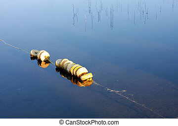 Bouys in Still Water - Floating buoys in glass like water ...