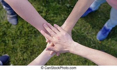 bovenzijde, handen, hun, anderen, het putten, achtergrond, elke, gras, vrienden, vrolijke
