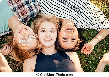 bovenzijde, het kijken, terwijl, fototoestel, modieus, het glimlachen, gras, vrienden, het liggen, aanzicht