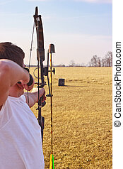 Bow At Target - Young man in a white t-shirt aiming loaded ...