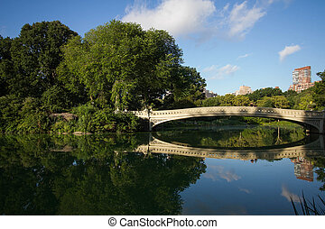 Bow bridge with shade and big trees reflect in lake with cloudy sky at Central Park