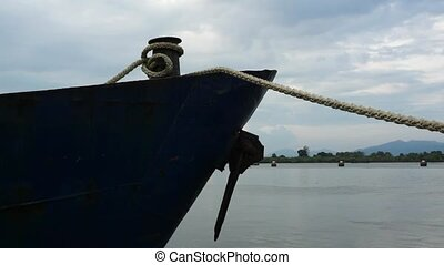 Bow of blue metal ship moored