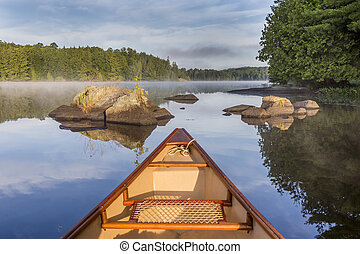 Bow of canoe on a lake in early morning - Ontario, Canada