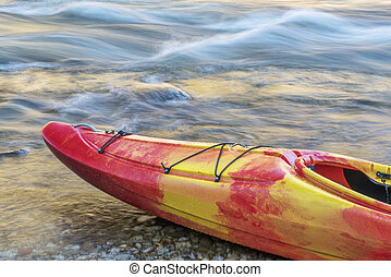 Bow of whitewater kayak on a river shore with a rapid in...