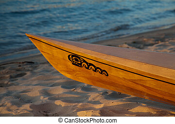 Bow of wooden kayak on beach - Sunset rays hitting the ...