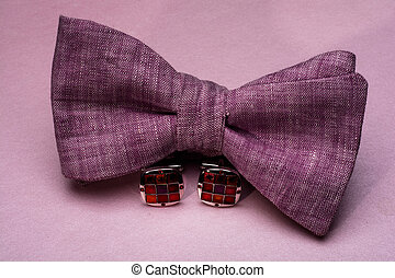 bow tie with cuff links on a pink background