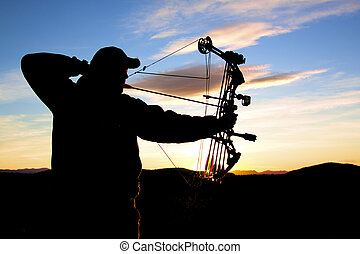 Bowhunter at Sunrise - a bowhunter at full draw at sunrise