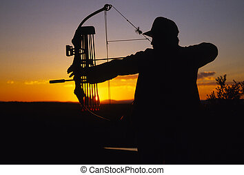 Bowhunter in Sunset - a bowhunter at full draw silhouetted...