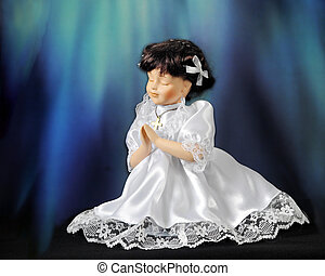 Bowing in Prayer - A praying doll in a communion dress. Rays...