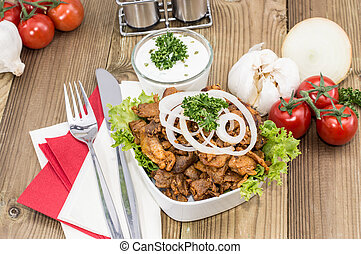 Bowl filled with Kebab meat on wooden background