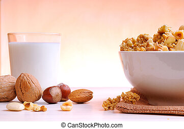 Bowl full of cereal with dried fruits and glass of milk at the bottom