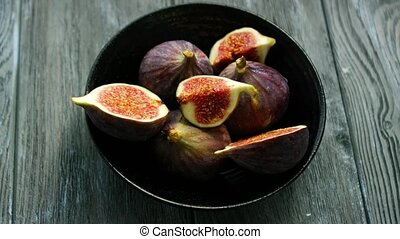 Bowl full of cut figs - From above shot of simple black bowl...