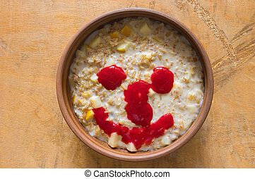 Bowl full of oatmeal cooked with milk and pear pieces and flavored with raspberry fresh smile