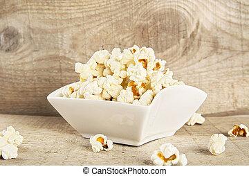 Bowl full of popcorn on wooden background