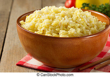 bowl full of rice on wooden background