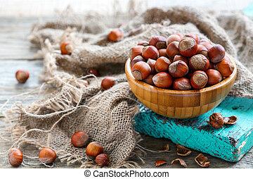 Bowl full of ripe hazelnuts on old green board.
