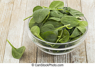 bowl of baby spinach - glass bowl of fresh baby spinach on a...