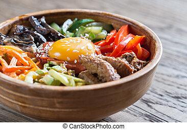 Bowl of bibimbap on the wooden table - Bowl of bibimbap