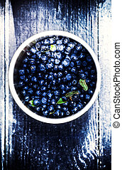 Bowl of Blueberries on wooden background closeup top view.