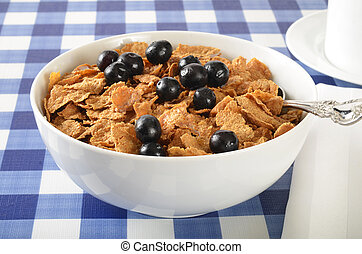 A bowl of bran flakes with coffee on a picnic table