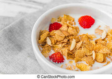 Bowl of breakfast cereals with milk and strawberries.