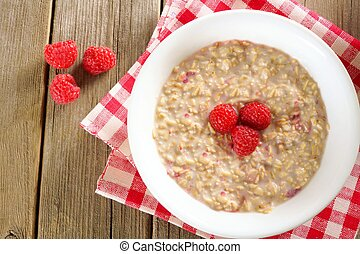 Bowl of breakfast oatmeal with raspberries. Overhead view on...