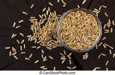 Bowl of brown rice groats on black wooden background. Top view