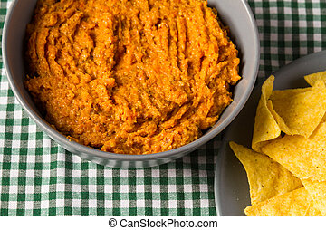 Bowl of carrot hummus with tortilla chips - Bowl of homemade...