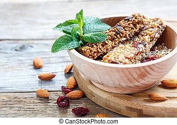 Bowl of cereal bars, nuts, dried fruits and honey.
