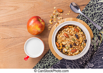 Bowl of cereal, cup of milk, and an apple on wooden table