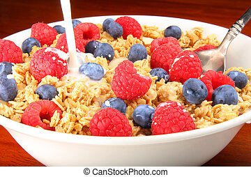 Delicious bowl of granola cereal with raspberries, blueberries and milk