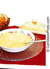 Bowl of chicken noodle soup with bread and butter