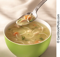 bowl of chiken soup - bowl on a table with chiken soup and a...