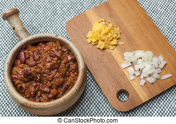 Bowl of chili with cheese and onions on side.